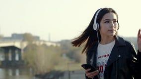 Aziatische mengen-ras donkerbruine tiener die aan muziek met haar hoofdtelefoons luisteren stock videobeelden