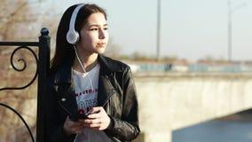 Aziatische mengen-ras donkerbruine tiener die aan muziek met haar hoofdtelefoons luisteren stock video