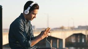 Aziatische mengen-ras donkerbruine tiener die aan muziek met haar hoofdtelefoons luisteren openlucht stock video
