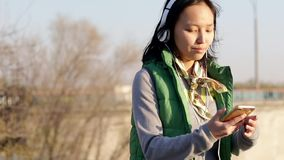 Aziatische mengen-ras donkerbruine tiener die aan muziek met haar hoofdtelefoons luisteren stock footage