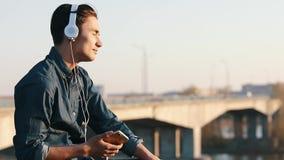 Aziatische mengen-ras donkerbruine tiener die aan muziek met zijn hoofdtelefoons luisteren stock video