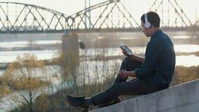 Aziatische mengen-ras donkerbruine tiener die aan muziek met zijn hoofdtelefoons luisteren stock videobeelden