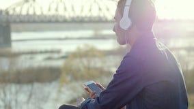 Aziatische mengen-ras donkerbruine tiener die aan muziek met zijn hoofdtelefoons luisteren stock footage