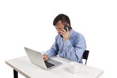 Aziatische mens die aan laptop en een slimme telefoon werken Royalty-vrije Stock Afbeeldingen