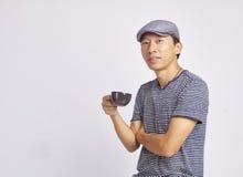 Aziatische mens die bij geïsoleerde de koffiekop glimlachen van de cameraholding Stock Foto's
