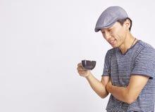 Aziatische mens die bij kop van koffie glimlachen die op wit wordt geïsoleerd Royalty-vrije Stock Foto's