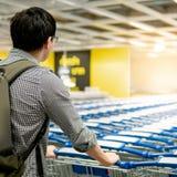 Aziatische mens die boodschappenwagentje in supermarkt trekken royalty-vrije stock fotografie