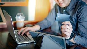 Aziatische mens die creditcard voor online het winkelen gebruiken stock afbeelding