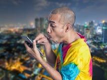 Aziatische mens die digitale tablet met het overdrijven op defocusstad houden Royalty-vrije Stock Afbeelding