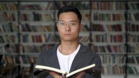 Aziatische mens die een blocknote status houden kijkend vooruit recht in de bibliotheek stock videobeelden