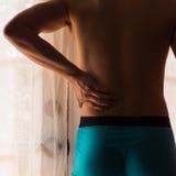 Aziatische mens die een lagere rugpijn heeft stock afbeeldingen
