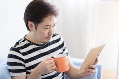 Aziatische mens die een mok houden en een boek lezen royalty-vrije stock foto