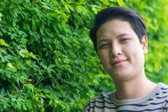 Aziatische mens die en zijn het gelukkige glimlachen bevinden zich tonen stock foto's