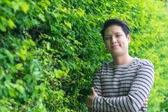 Aziatische mens die en zijn het gelukkige glimlachen bevinden zich tonen stock foto