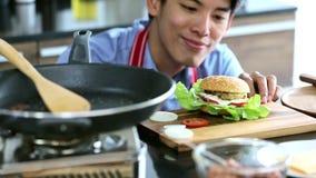 Aziatische mens die en zo trots van zijn hamburger glimlachen stock footage