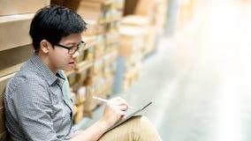 Aziatische mens die inventarisatie op tablet in pakhuis doen stock afbeelding