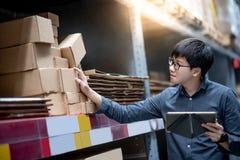 Aziatische mens die inventarisatie op tablet in pakhuis doen stock foto