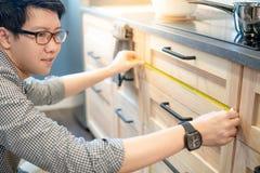 Aziatische mens die meetlint op keukenteller gebruiken stock afbeelding