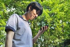 Aziatische mens die mobiele telefoon met behulp van Stock Fotografie