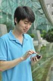 Aziatische mens die mobiele telefoon met behulp van Stock Afbeeldingen