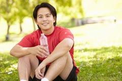 Aziatische mens die na oefening rusten Stock Afbeelding