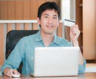 Aziatische mens die online winkelen Stock Afbeeldingen