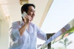 Aziatische mens die op balkon met mobiele telefoon telefoneren Royalty-vrije Stock Foto