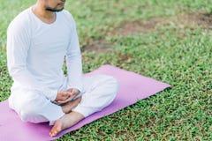 Aziatische mens die op groen gras in het park, de rust en het geconcentreerde, concept van de gezondheids en yogameditatie, met e Royalty-vrije Stock Foto's