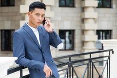 Aziatische mens die op telefoon in de straat spreken royalty-vrije stock foto's