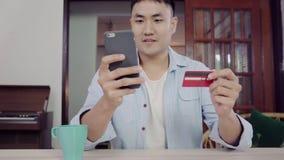 Aziatische mens die smartphone voor online het winkelen en creditcard in Internet gebruiken bij woonkamerhuis stock footage