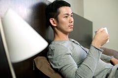 Aziatische Mens die thee/koffie in bed heeft stock foto's