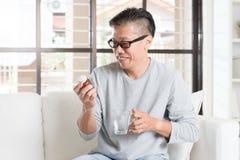 Aziatische mens die vitaminen eten Stock Foto's