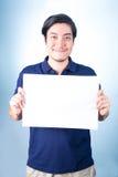 Aziatische mens die zich met leeg horizontaal leeg document in handen bevinden, o Stock Afbeeldingen