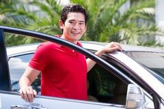 Aziatische mens die zich voor auto bevinden Stock Afbeelding