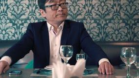 Aziatische mens in kostuumzakenman die in de koffie hun voedsel wachten Lang wacht op het opdracht geven tot zenuwachtig stock video