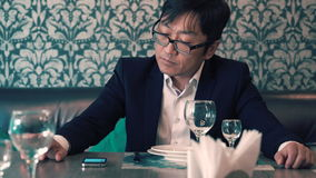 Aziatische mens in kostuumzakenman die in de koffie hun voedsel wachten Lang wacht op het opdracht geven tot zenuwachtig stock videobeelden
