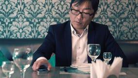 Aziatische mens in kostuumzakenman die in de koffie hun voedsel wachten Lang wacht op het opdracht geven tot zenuwachtig stock footage