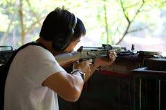 Aziatische mens met een geweer in klaar positie stock afbeeldingen