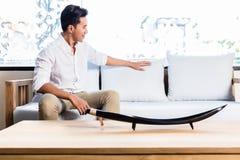 Aziatische mens op banklaag in meubilairopslag stock foto