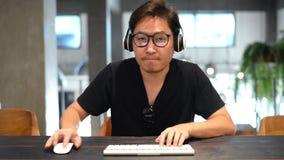 Aziatische mens voor computerpersen op de sleutels en de bewegingen de muis stock footage