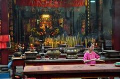 Aziatische mensen die en wierookstokken in een pagode bidden branden Stock Afbeelding
