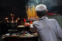 Aziatische mensen die en wierookstokken in een pagode bidden branden Stock Foto's