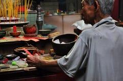 Aziatische mensen die en wierookstokken in een pagode bidden branden Stock Foto
