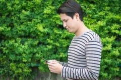 Aziatische mensenzitting en het gebruiken van smartphone royalty-vrije stock afbeeldingen