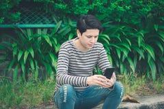 Aziatische mensenzitting en het gebruiken van smartphone royalty-vrije stock fotografie