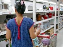 Aziatische moeder die die een boodschappenwagentje duwen met goederen en haar kleine babys wordt gevuld stock afbeelding