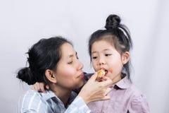 Aziatische Moeder die een dochter voeden stock fotografie
