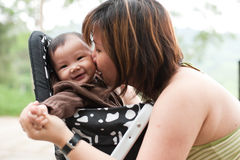 Aziatische moeder die haar meisje van de 7 maand oud baby kust Stock Foto's