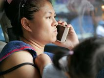 Aziatische moeder die ongemakkelijk een telefoongesprek maken terwijl het behandelen van haar dochter in een drijfauto stock afbeeldingen