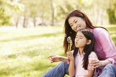 Aziatische moeder en dochter blazende bellen in park Stock Foto's